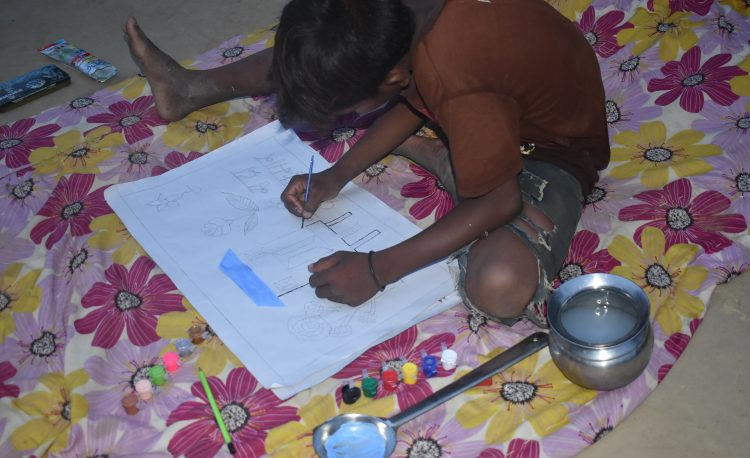 A student drawing his house during painting competition